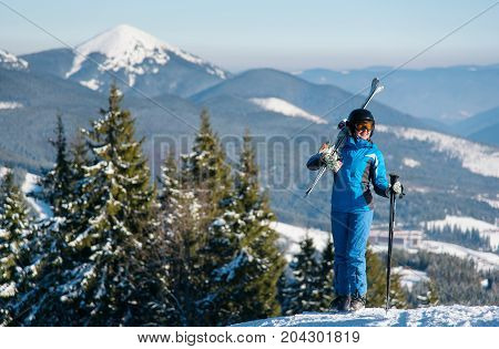 Happy Female Skier Standing On Top Of A Mountain With Skis On Her Shoulder Stunning Scenery. Mountai
