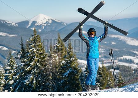 Happy Woman Skier Holding Her Skis Over Head, Wearing Blue Ski Suit And Black Helmet Standing On Top