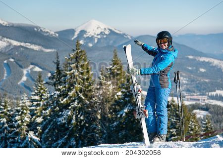 Shot Of A Female Skier Standing On Top Of A Mountain With Skis At Winter Resort, Smiling, Pointing A