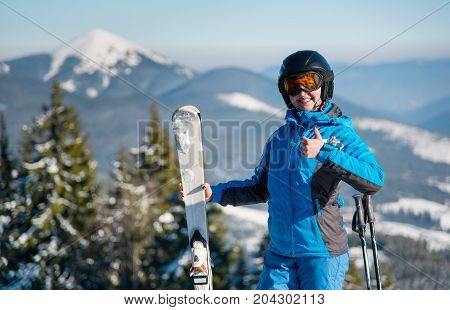 Close-up Portrait Of Happy Female Skier Showing Thumbs Up On Top Of A Mountain With Her Skis, Smilin