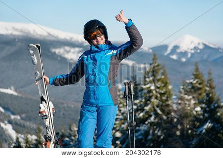 Shot Of A Happy Female Wearing Skiing Gear Smiling Showing Thumbs Up Posing In The Mountains Enjoyin