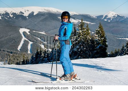 Happy Female Skier Resting On The Top Of The Mountain At Ski Resort, Wearing Blue Ski Suit, Mask And
