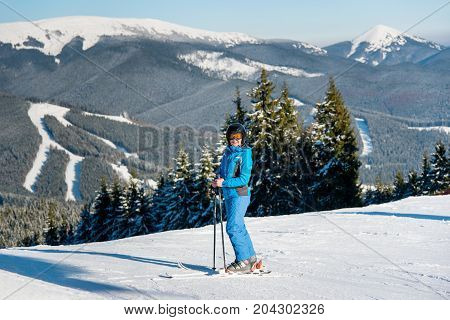 Full Length Shot Of A Happy Woman Skier Skiing On The Slope At Winter Ski Resort In Sunny Beautiful