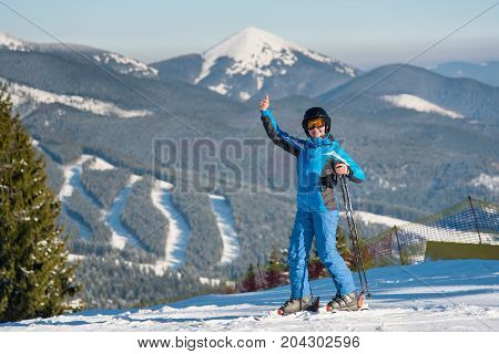 Full Length Shot Of A Happy Woman Skier Smiling Joyfully To The Camera, Showing Thumbs Up While Skii