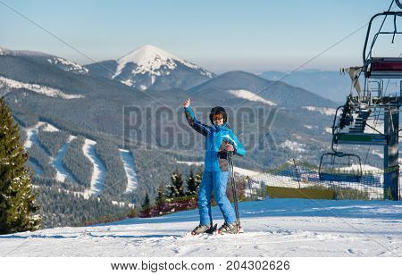 Full Length Shot Of A Smiling Female Skier Showing Thumbs Up While Skiing On The Snowy Slope At The