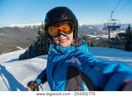 Close-up Portrait Of Happy Woman Skier Smiling, Taking A Selfie While Resting On The Slope After Ski