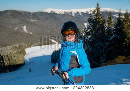 Shot Of A Female Skier Smiling To The Camera Joyfully While Skiing On The Snowy Slope In The Mountai