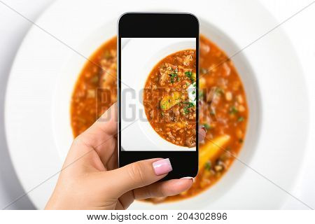 Smartphone camera hand point shoot photo soup. Food photograph. Made for social networks. Top view mobile phone