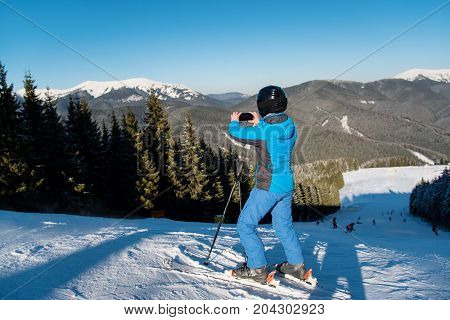 Rearview Full Length Shot Of A Woman Skier Using Her Smart Phone Taking Photos Of Stunning Winter Sc