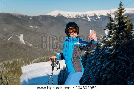 Horizontal Shot Of A Female Skier Smiling Using Her Smart Phone Taking Photos Of Stunning Winter Sce