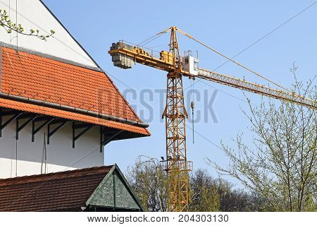 Tower crane at the construction site next to a building