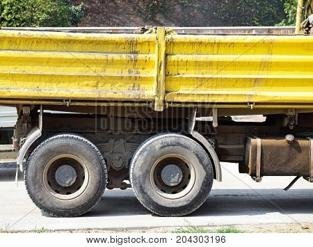 Part of a yelllow truck at the road construction
