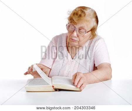Old Woman In Glasses Reads The Book On A White Background