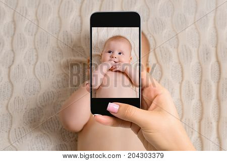 Happy mother taking a picture of her baby girl in crib with smart phone. Made for social networks. Top view mobile phone