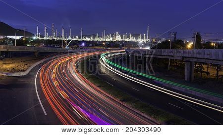 beautiful lighting of oil refinery plant in heavy petrochemical industry estate use for powerRoad to the oil refiner on blue sky in twilight time background