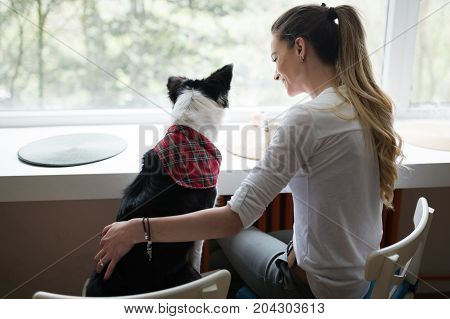 Beautiful woman playing at home with happy dog