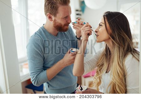 Beautiful couple having fun and laughing at home while eating ice cream