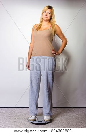 Diet fitness slimming loosing weight concept. Happy blonde woman wearing tracksuit standing on weighing machine