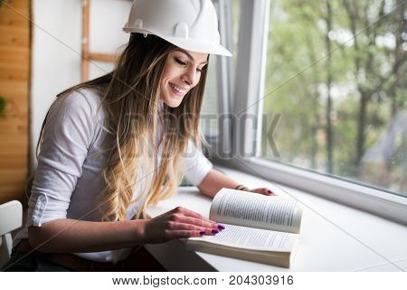 Beautiful woman reading and studying for university exams concept image
