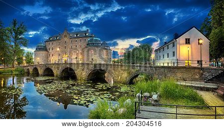 Panoramic HDR image of Orebro Castle and bridge reflecting in water of Svartan river at dusk Sweden