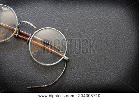 Old stylish spectacles closeup on black stone background