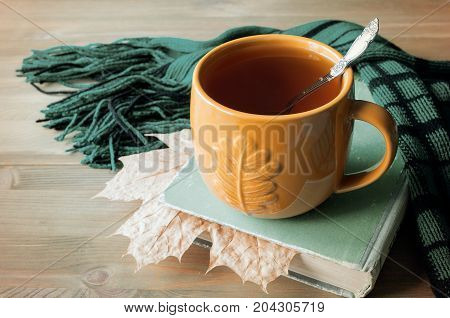 Autumn still life. Cup of tea, book with maple autumn leaf and warm scarf on the wooden table. Autumn background.Autumn concept. Still life with autumn mood.Autumn still life in retro tones.Autumn background.