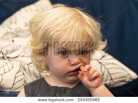 Blond haired girl with finger in mouth due to toothache