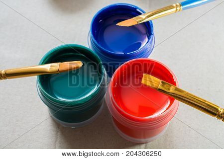 Art brushes and few jars with acrylic paint. Three plastic jars.