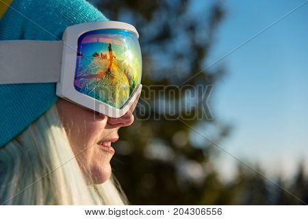 Close-up Profile Shot Of A Smiling Female Snowboarder Wearing Skiing Mask, Looking Away, Resting In