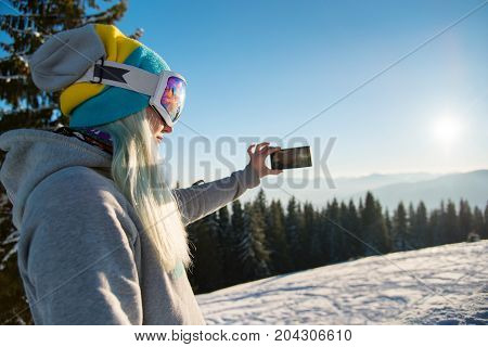 Shot Of A Female Snowboarder Using Her Smart Phone While Resting After Snowboarding, Taking Photos O