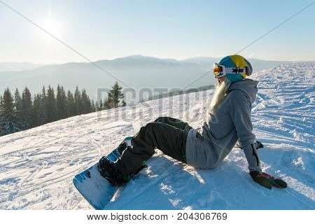 Female Snowboarder Sitting On The Snowy Slope In The Evening, Smiling, Enjoying Sunny Day In The Mou