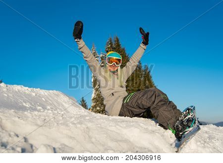 Low Angle Shot Of A Happy Young Woman Snowboarder Sitting On Top Of The Slope, Smiling To The Camera