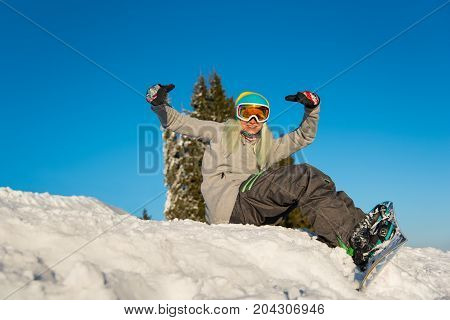 Smiling Young Female Snowboarder Sitting And Having Fun On Top Of The Snowy Slope Outdoors On A Beau