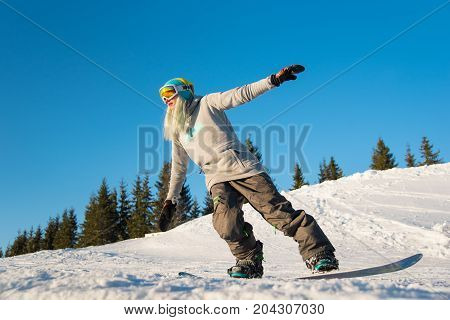 Full Length Shot Of A Blonde Haired Woman Snowboarding In The Mountains On A Beautiful Sunny Winter