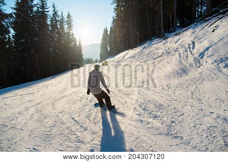 Rearview Shot Of A Snowboarder Riding The Snowy Slope On A Beautiful Winter Sunny Evening At Winter