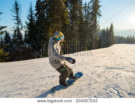 Young Female Snowboarder Enjoying Skiing On The Mountain Slopes On A Sunny Winter Day At Ski Resort