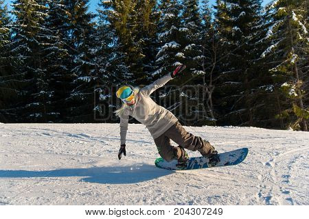 Young Female Snowboarder Enjoying Riding On The Snowy Slope On A Sunny Winter Day Copyspace