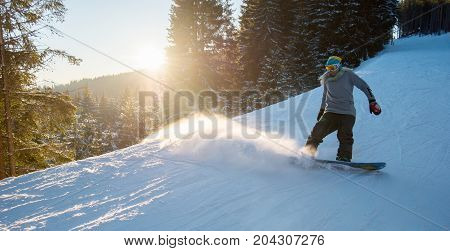 Full Length Shot Of A Female Snowboarder Skiing On Snowy Slope On The Dawn In The Mountain Ski Resor