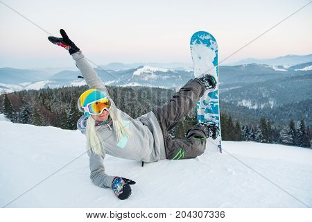 Shot Of A Happy Young Woman Snowboarder Lying On The Snow Having Fun Outdoors Resting In The Mountai