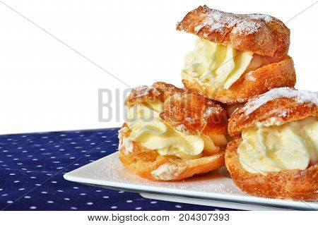 Cream puff with vanilla custard sprinkled with powdered sugar on white plate over napkin isolated on white background.