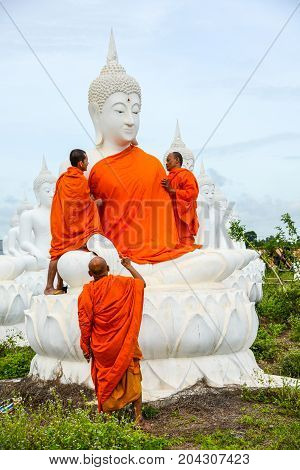 Sa Kaeo Thailand - July 14 2013: Monks dressing one of White Buddha Image with robes in Buddha Park of Sa Kaeo Thailand