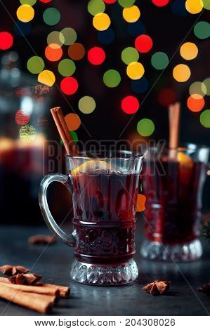 Traditional winter mulled wine in vintage glass and christmas ornament on lights background, selective focus and toned image. Sangria on holiday table. Celebration thanksgiving with spicy cocktail.