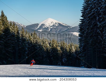 Man skier skiing downhill at ski resort against forest and mighty mountains. Male is wearing orange ski-suit helmet and goggles. Carpathian Mountains Bukovel