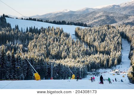 Skiers And Snowboarders Downhill Slope At The Winter Ski Resort On A Background Of Ski-lifts, Forest