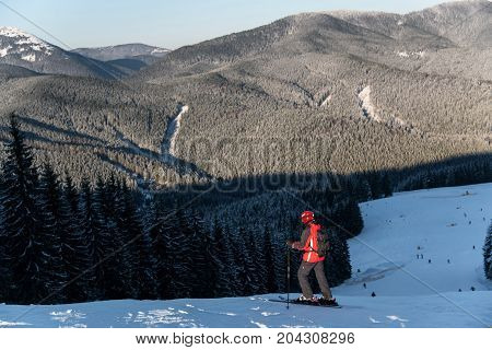 Rear View Of Male Skier With A Backpack Is At The Top Of The Descent Enjoying The Scenery Of Local M