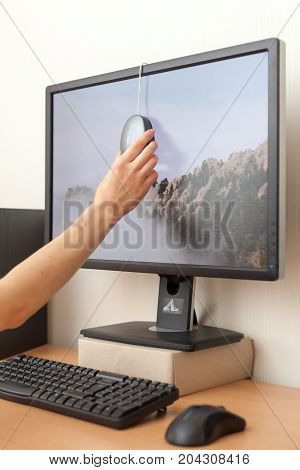 Workspace with calibrator or profiler attached to laptop's display to get accurate colors. Woman hand installs the calibrator on the monitor to adjust the color.
