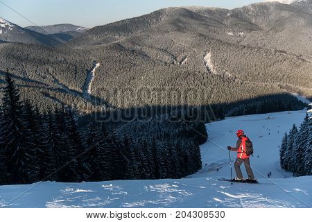 Skier With A Backpack Is At The Top Of The Slope Enjoying The Scenery Of Local Mountains And Forests