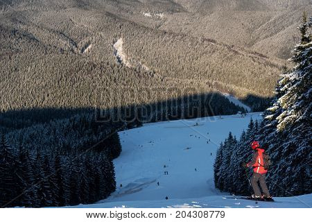 Skier With A Backpack Is At The Top Of The Descent Getting Ready To Skiing. The Guy Is Dressed In A
