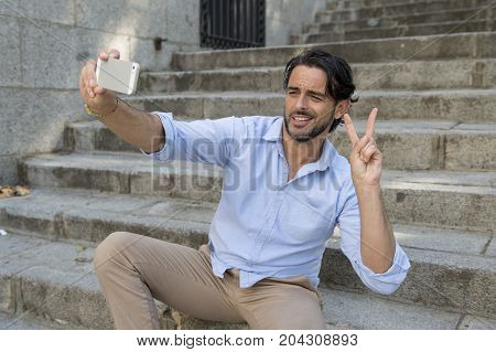 Young Attractive Latin Man On City Staircase Taking Selfie Picture Having Fun On Mobile Phone