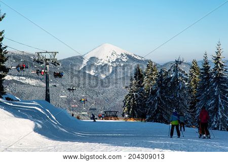 Skiers At The Ski Resort On A Background Of Ski-lifts, Forests, Mountains At The Sunny Day. Ski Seas